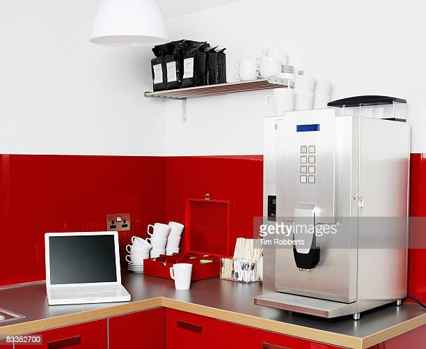 Laptop and coffee machine in office kitchen