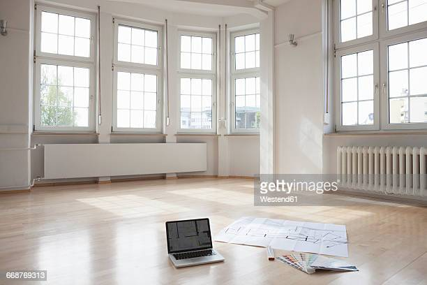 Laptop and construction plan on floor in empty apartment