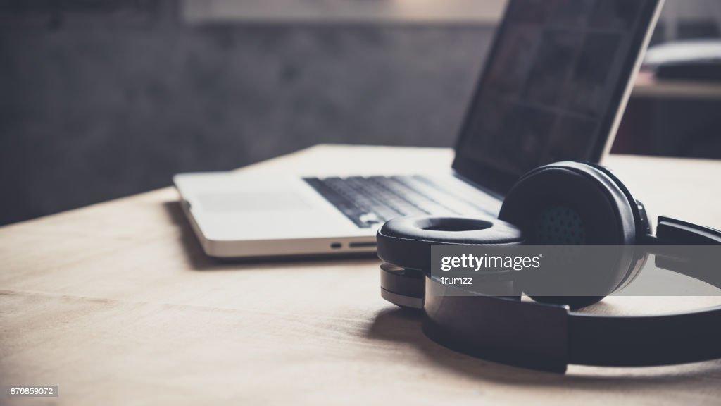 Laptop und Kopfhörer auf Holztisch zu Hause. : Stock-Foto