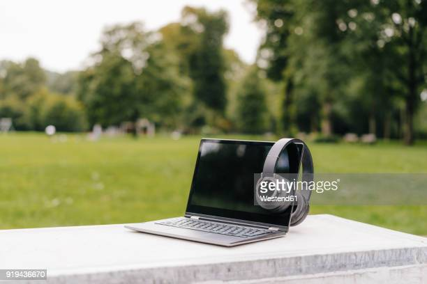 Laptop and headphones on a wall in a park