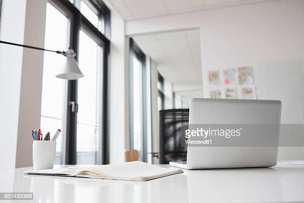 laptop and notebook on office desk - schreibtisch stock-fotos und bilder