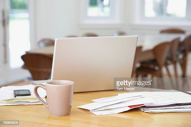laptop and paperwork on kitchen counter with mug - flexplekken stockfoto's en -beelden