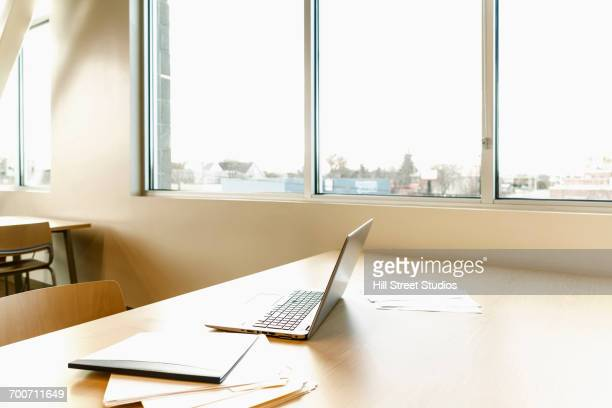 Laptop and paperwork on table near window