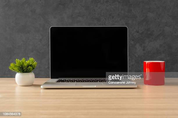 laptop and red coffee mug on office desk - laptop stock pictures, royalty-free photos & images