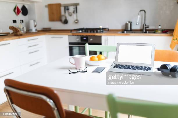 laptop and smartphone on the kitchen table - website template stock photos and pictures