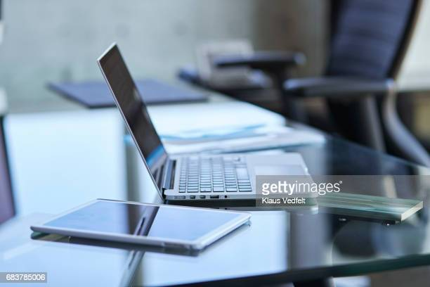 Laptop and tablet on glass table