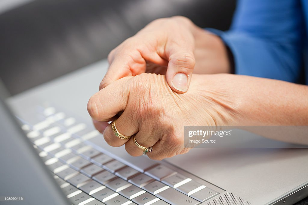 Laptop and woman with pain in hand : Stock Photo