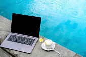 laptop at swimming pool with cup