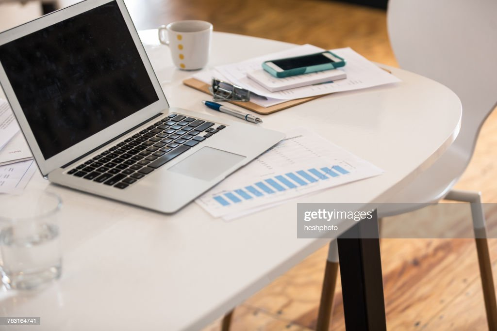 Laptop, bar chart and smartphone on office desk : Stock Photo