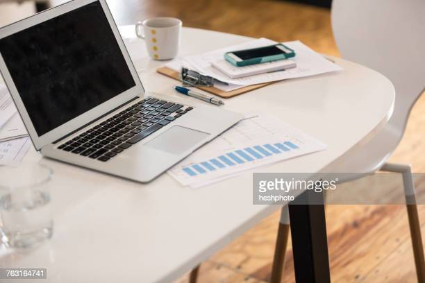 laptop, bar chart and smartphone on office desk - heshphoto stock pictures, royalty-free photos & images