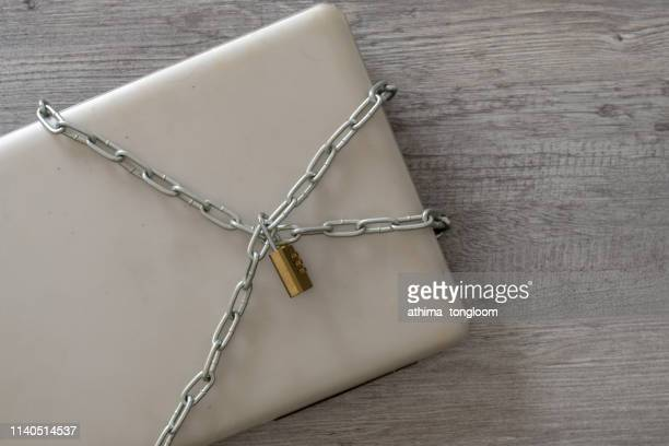 a laptop chained and padlocked in an attempt to keep it safe. - data privacy stock pictures, royalty-free photos & images