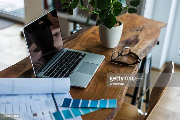 Laptop, color samples and glasses on wooden desk