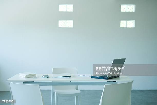 Laptop computer and cell phone on desk in office