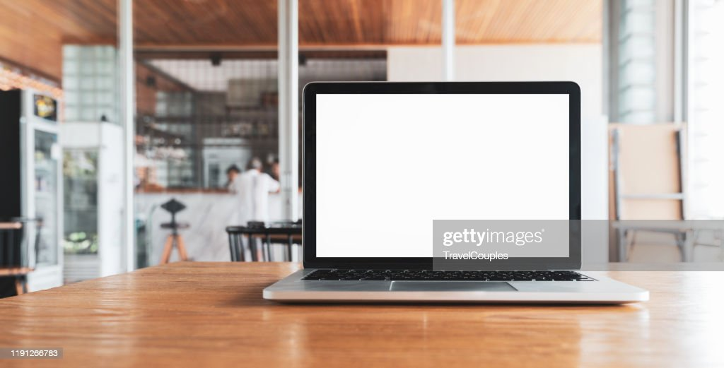 Laptop computer blank white screen on table in cafe background. Laptop with blank screen on table of coffee shop blur background. : Photo