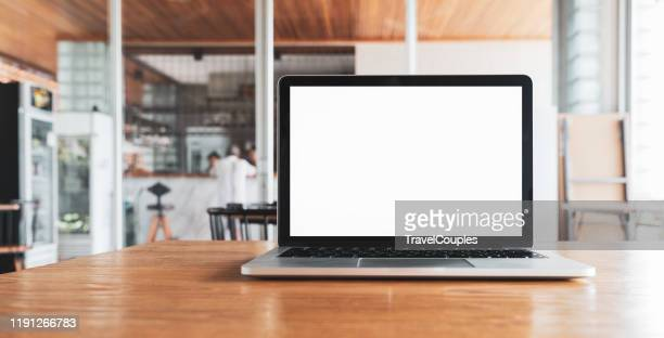 laptop computer blank white screen on table in cafe background. laptop with blank screen on table of coffee shop blur background. - personal computer foto e immagini stock