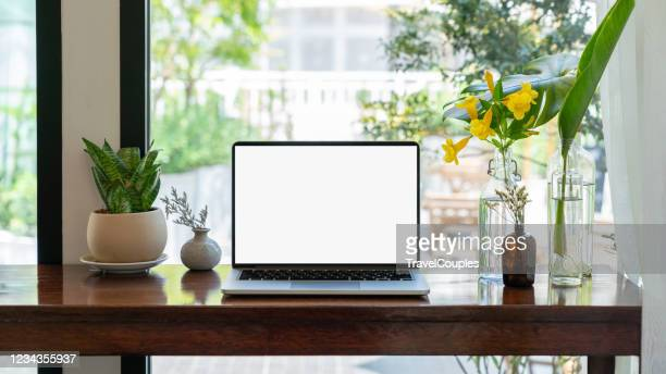 laptop computer blank white screen on table in cafe background. laptop with blank screen on table of coffee shop blur background. - schermo foto e immagini stock