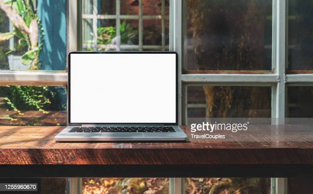 laptop computer blank white screen on table in cafe background. laptop with blank screen on table of coffee shop blur background. - laptop stock-fotos und bilder