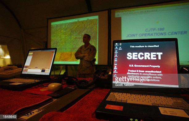 A laptop computer displays a message as US Army General Dan McNeill Coalition Joint Task Force 180 commander speaks to the news media inside the...