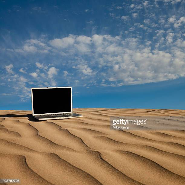Laptop computer on desert sand