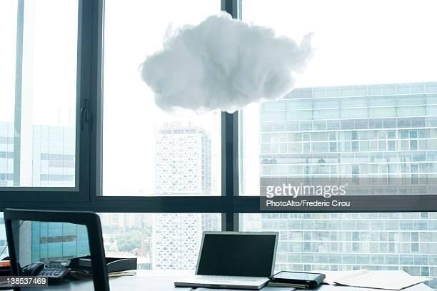 Laptop computer on desk, cloud above laptop computer