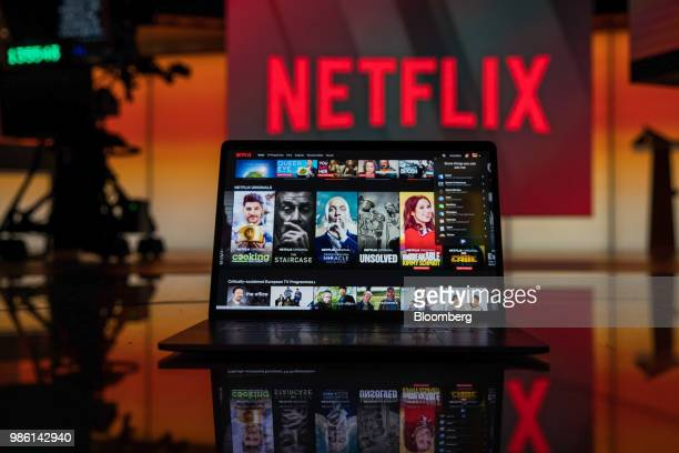 A laptop computer screen displaying the Netflix homepage stands against an illuminated screen bearing the company logo in this arranged photograph in...
