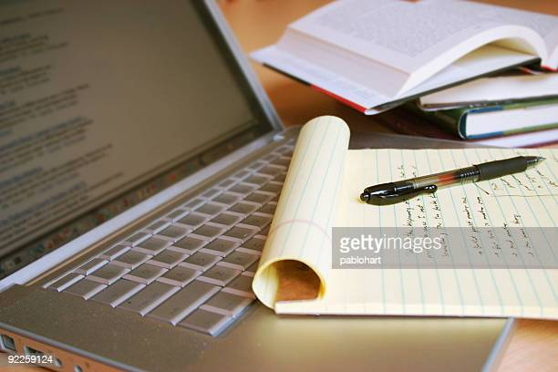 laptop computer with books, pen and yellow legal pad - bericht stockfoto's en -beelden