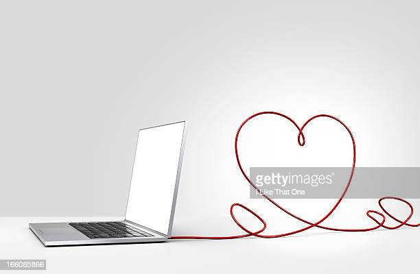 laptop computer with cable forming a heart - atomic imagery 個照片及圖片檔
