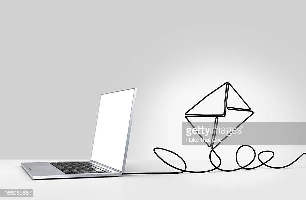 laptop computer with cable forming a n envelope - e mail foto e immagini stock