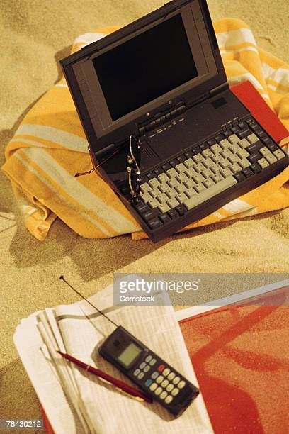 Laptop computer with cell phone and newspaper at the beach