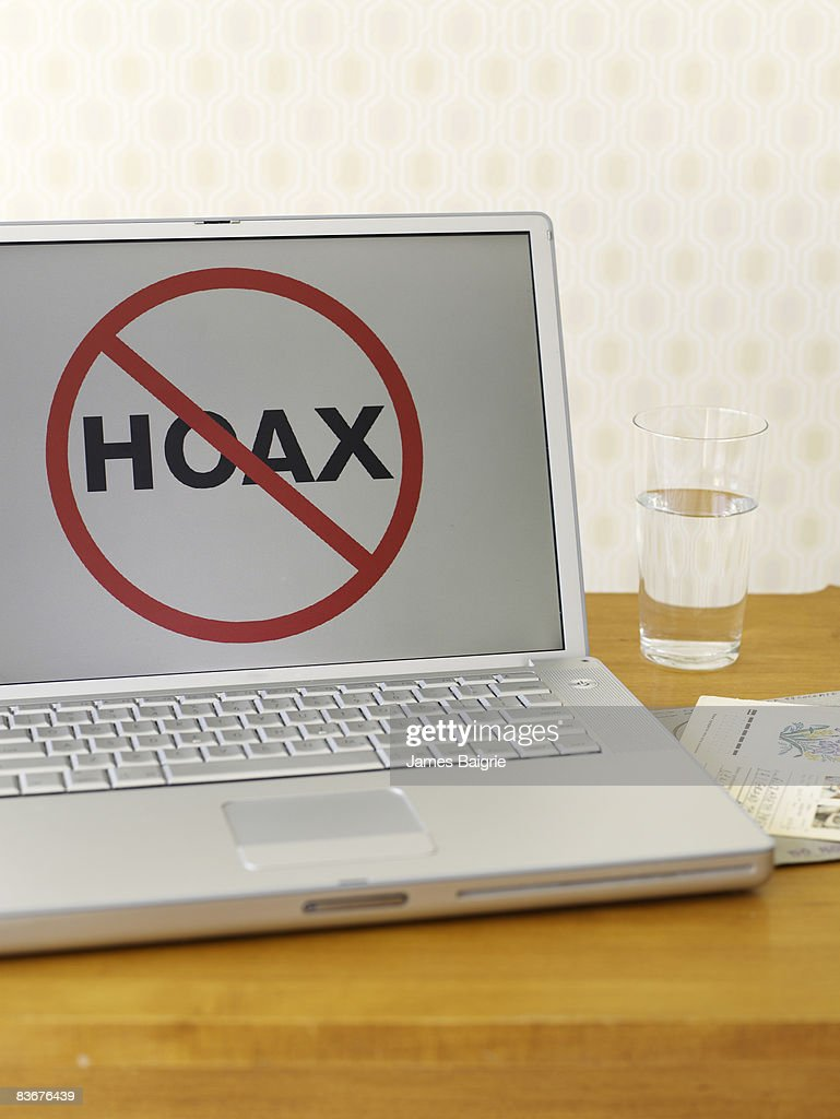 Laptop computer with HOAX sign on screen : Stock Photo