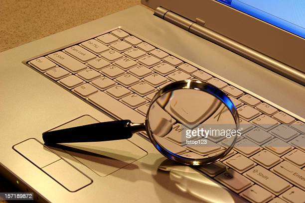 Laptop Computer with magnifying glass on keyboard.