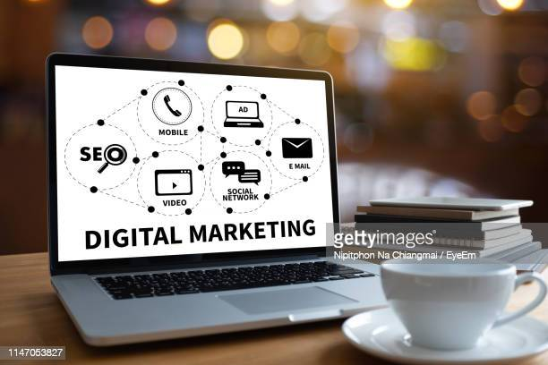 laptop displaying digital marketing diagram with books and coffee cup on table - digital marketing stock pictures, royalty-free photos & images