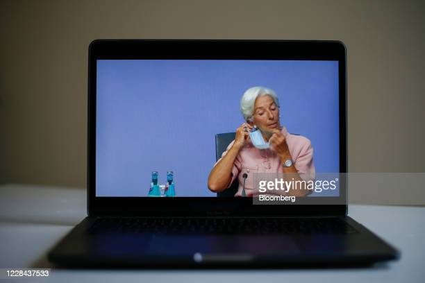 A laptop displays Christine Lagarde president of the European Central Bank removing a face mask during a live stream video of the central bank's...