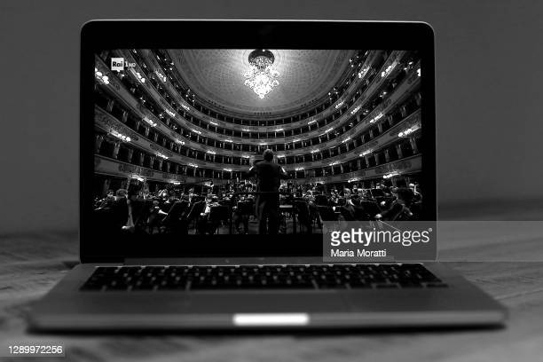 Laptop displays the orchestra at the premiere of the Teatro alla Scala in Milan, this year recorded and behind closed doors due to the coronavirus...