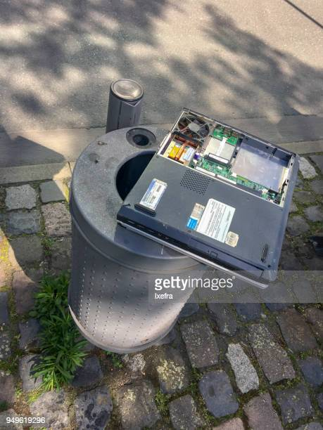A laptop disposed on trash bin.