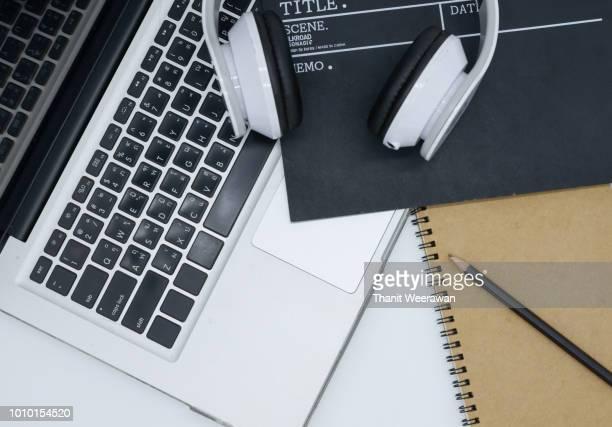 laptop, earphone, Movie clapper board, note pad on white background, Creative, director idea.