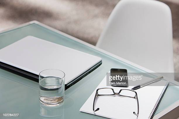 Laptop, eyeglasses, cell phone and notepad on table