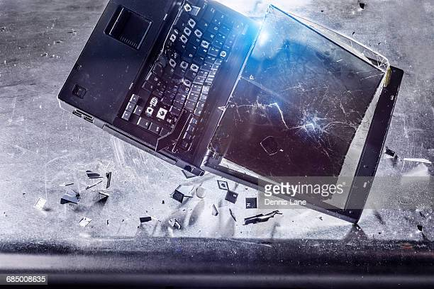 Laptop falling and shattering on desk