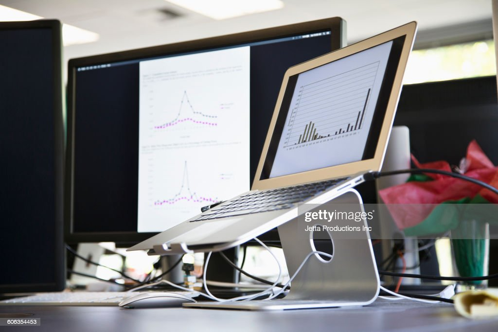 Laptop in stand on office desk : Stock Photo