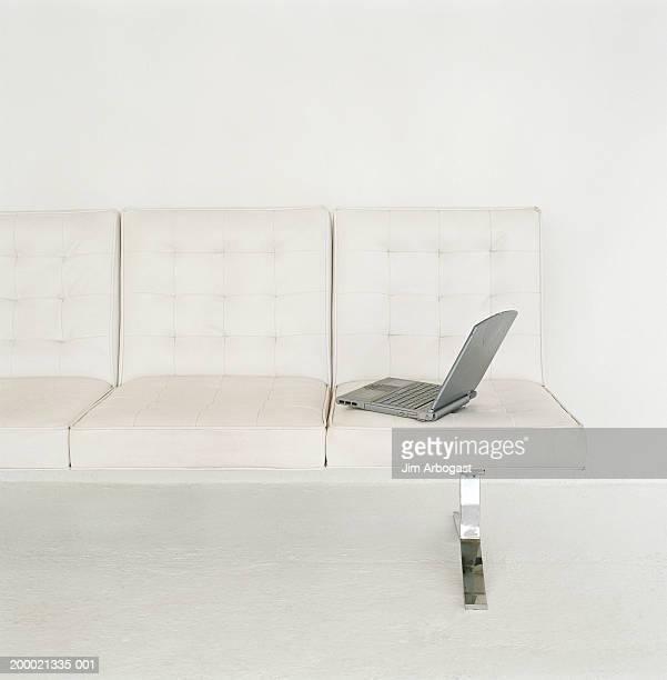 Laptop left sitting on sofa
