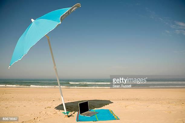 A laptop lying on a beach towel on a beach