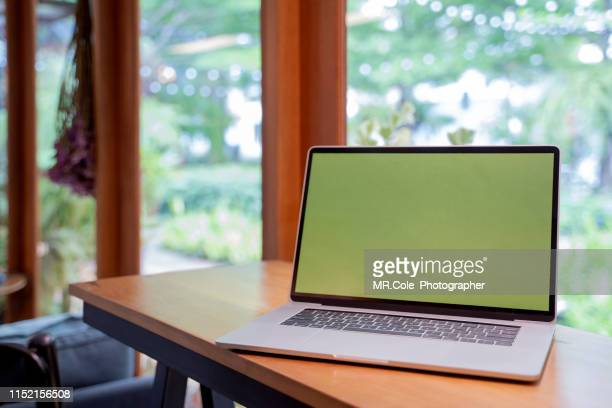laptop mock up with green screen in coffee shop - chroma key foto e immagini stock