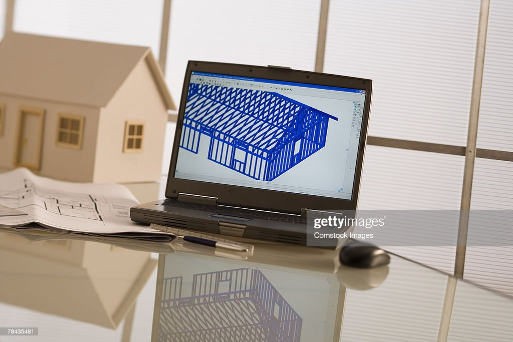 Laptop, model house, and blueprints : Stockfoto