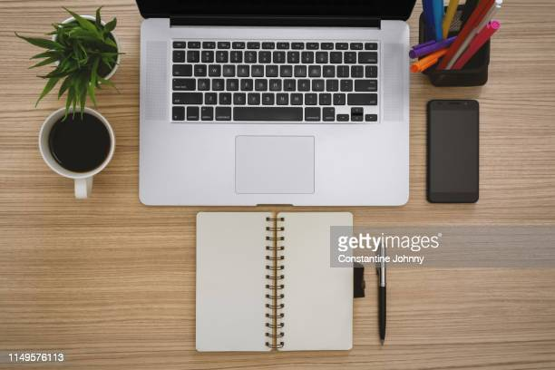 laptop, notebook and office supply items on wooden work desk - neat stock pictures, royalty-free photos & images
