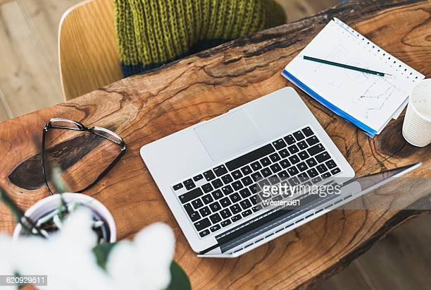 Laptop, notepad and glasses on wooden desk