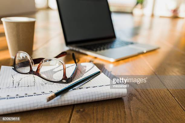 Laptop, notepad and glasses on wooden floor