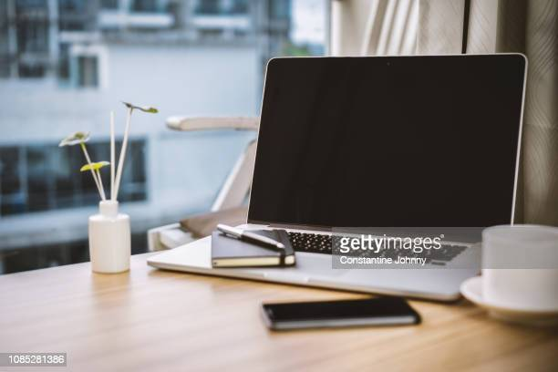 laptop, notepad, coffee cup and mobile phone on wood table at home office - bureau stockfoto's en -beelden