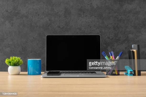 laptop, office supply items and blue coffee mug on office desk. - neat stock pictures, royalty-free photos & images