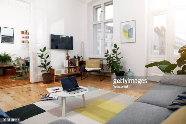 laptop on a coffee table in a modernly furnished flat - niemand stock-fotos und bilder