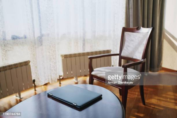 laptop on a table in domestic room - arman zhenikeyev stock pictures, royalty-free photos & images